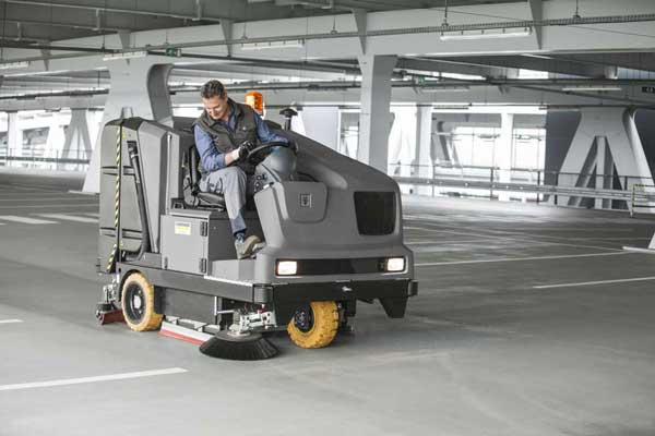 Combination sweeper scrubber cleaning a car park