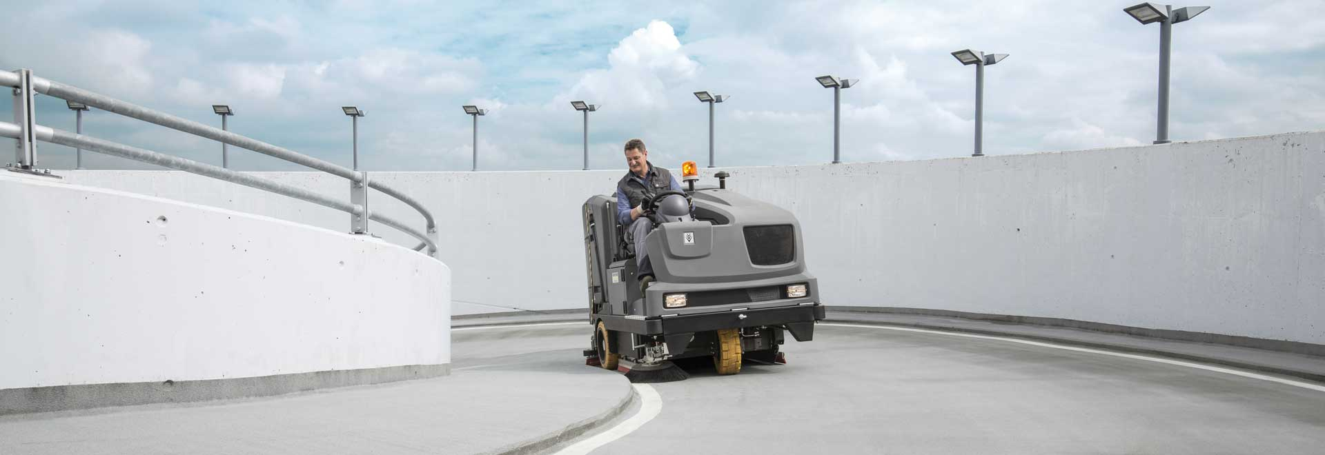 Ride on sweeper cleaning tarmac