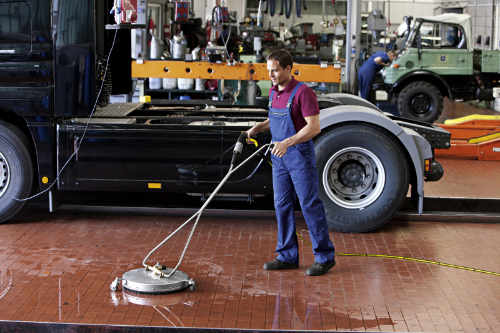 Man cleaning a car workshop floor
