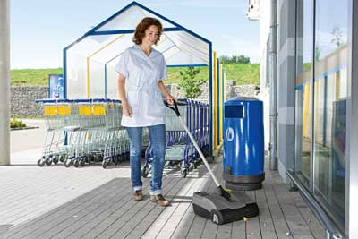 Handheld floor sweeper cleaning a shop entrance