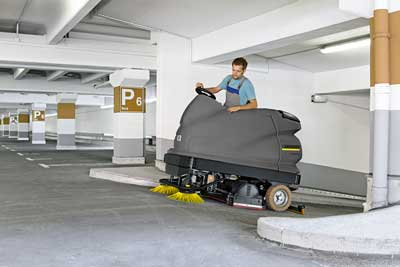Scrubber dryer cleaning a car park