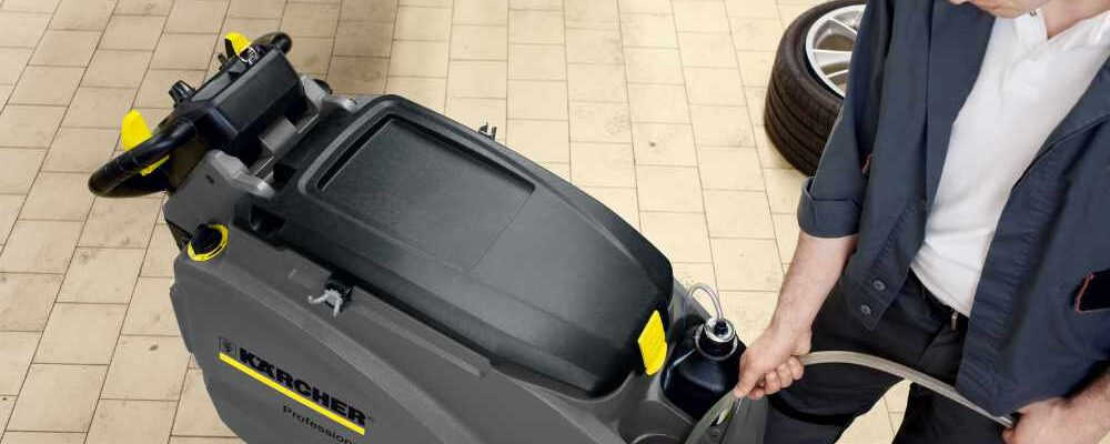 Filling a scrubber dryer with detergent and water