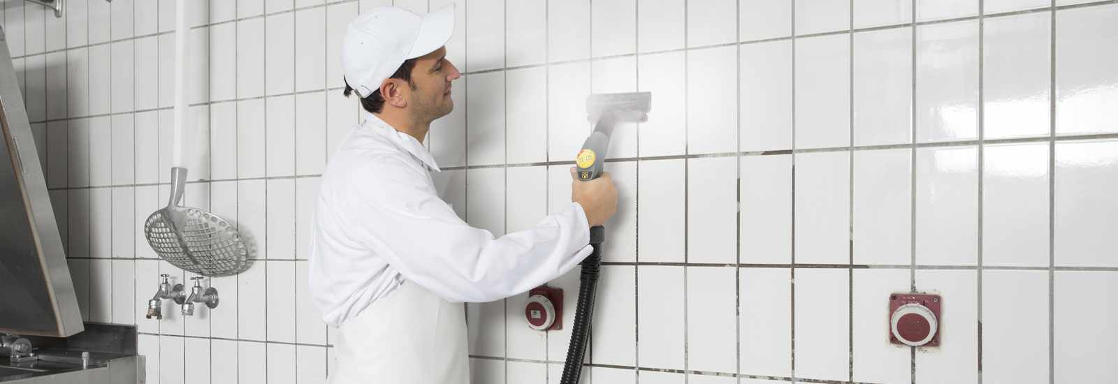 steam cleaning tiled walls in a commercial kitchen